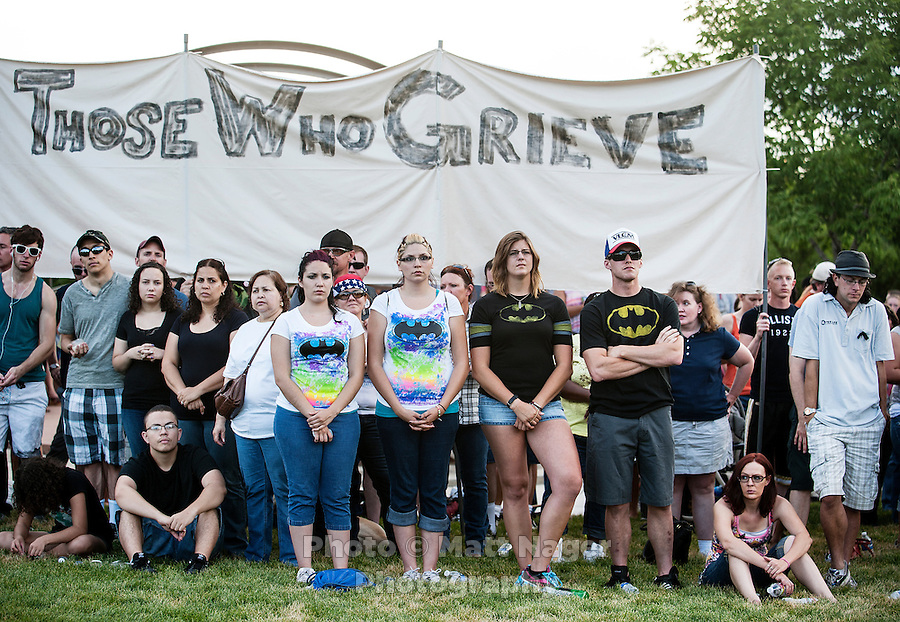In Batman shirts from left, Sharayah Angel (cq), 18, Analisa Angel (cq), 18, Paige Morris (cq), 23, and Drew Griffith (cq), 26, pray for the 12 victims of the mass shooting at the Aurora Century 16 movie theater during a vigil at the Aurora Municipal Center, in Aurora, Colorado, Sunday, July 22, 2012. Suspect James Holmes, allegedly went on a shooting spree and killed 12 people and injured 59 during an early morning screening of 'The Dark Knight Rises.'..Photo by MATT NAGER