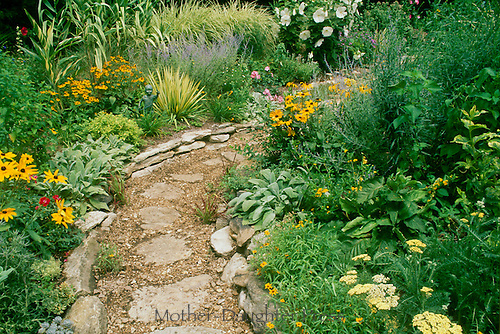 Garden path of stone and gravel curves through a private section decorated with yellow blooming flowers and annuals