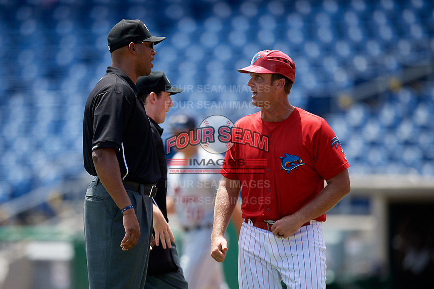 Clearwater Threshers manager Shawn Williams (11) talks with umpires Jose Navas and Tyler Jones during the first game of a doubleheader against the Lakeland Flying Tigers on June 14, 2017 at Spectrum Field in Clearwater, Florida.  Lakeland defeated Clearwater 5-1.  (Mike Janes/Four Seam Images)
