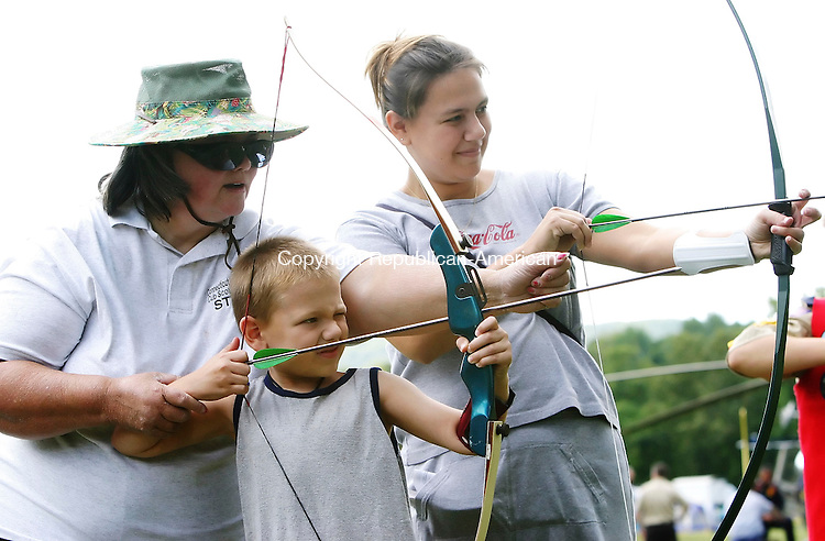 NAUGATUCK, CT- 10 SEPTEMBER 2005-091005BZ01- Volunteer Sarah White, a certified archery instructor, left, helps Justin Scully, 7, of Naugatuck, take aim while using a bow and arrow with his mother Crystal Scully during a Boy Scout and Cub Scout camp-out at Linden Park in Naugatuck Saturday.  Crystal Scully said her son will be joining the scouts this year.<br /> Jamison C. Bazinet / Republican-American