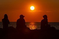 People sit on the jetty and watch the sunset over the Vineyard Sound at Menemsha Beach in Chilmark, Massachusetts on Martha's Vineyard.