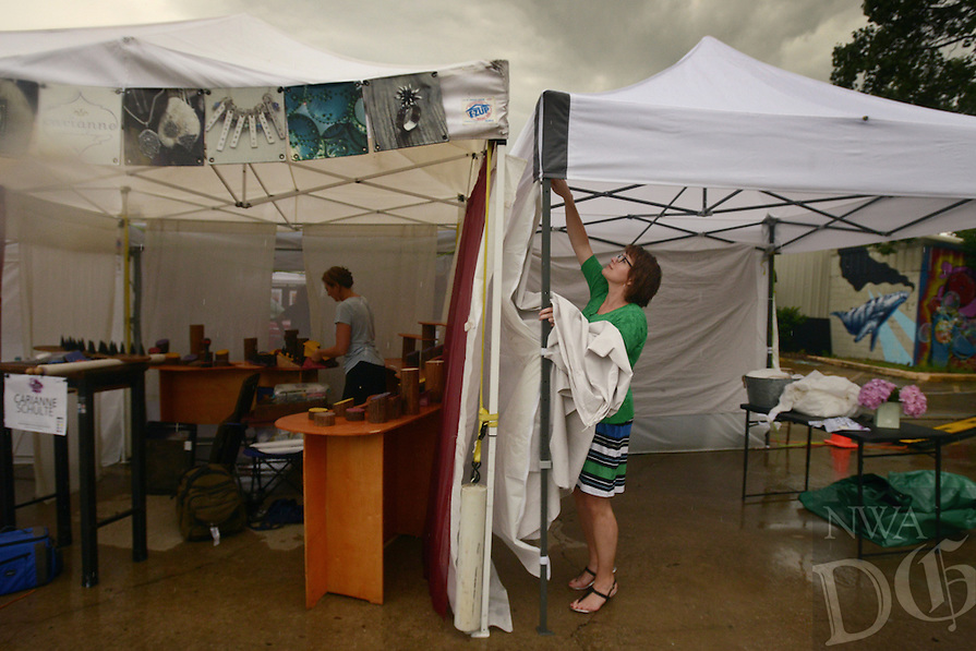 NWA Democrat-Gazette/BEN GOFF @NWABENGOFF<br /> Artists pack up their booths on Sunday June 12, 2016 after the Bentonville Art Market in downtown Bentonville was closed early due to rain and lightning. Stephens won 'Best of 3D' in the show, which is part of the Downtown Bentonville, Inc. Art and Culinary Festival.