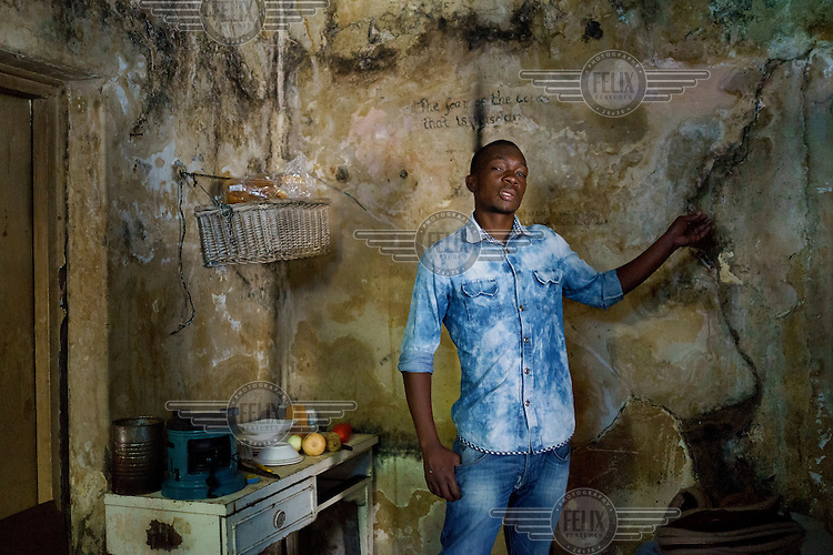 Oskido in his room in a 'hijacked building' (slang that describes an illegally occupied squat) in Hillbrow. The building has neither electricity nor running water, and the walls and surviving windows are blackened with soot from charcoal and kerosene stoves and lanterns.  Hillbrow, in downtown Johannesburg, is the city's most notorious neighbourhood. It is overcrowded, ridden with illegal squats and suffers from high levels of crime much of which is related the thriving illicit drug trade.
