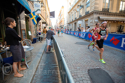 25 AUG 2013 - STOCKHOLM, SWE - Sven Riederer (SUI) (right) of Switzerland runs through the streets of Gamla Stan, the old part of Stockholm, Sweden, during the elite men's ITU 2013 World Triathlon Series round (PHOTO COPYRIGHT © 2013 NIGEL FARROW, ALL RIGHTS RESERVED)
