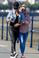 Pictured: Two ladies enjoy a walk along the beach front during the sunny weather at Mumbles, near Swansea, Wales, UK. Thursday 19 September 2019