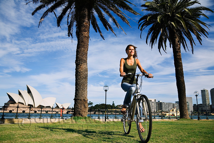 A young woman cycling around Sydney Cove.  Sydney, New South Wales, AUSTRALIA.
