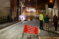 Pictured: A police officer watces on as a car attempts to pass the flooded closed off Old Station Road in Carmarthen, Wales, UK. Saturday 13 October 2018<br /> Re: River Towy has burst its banks and adjacent properties have flooded, caused by storm Callum, in Carmarthen, west Wales, UK.
