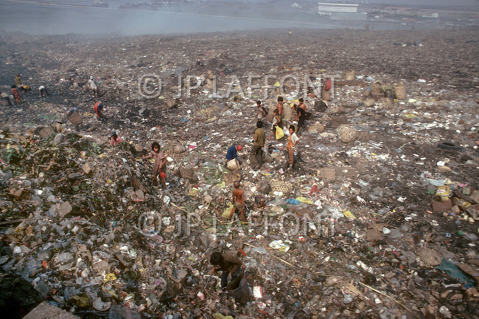 Children collect items for sale in a garbage dumb outside Manilla, Philippines - Child labor as seen around the world between 1979 and 1980 - Photographer Jean Pierre Laffont, touched by the suffering of child workers, chronicled their plight in 12 countries over the course of one year.  Laffont was awarded The World Press Award and Madeline Ross Award among many others for his work.