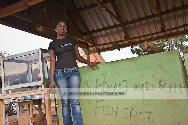 """A young woman grills fish at a roadside """"point and kill"""" fish stand in Millenium Park in Abuja, Nigeria."""