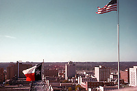 Vintage view of the Texas and US flags flying on top of Texas Capitol looking south over downtown Austin, circa 1960s - Stock Image.
