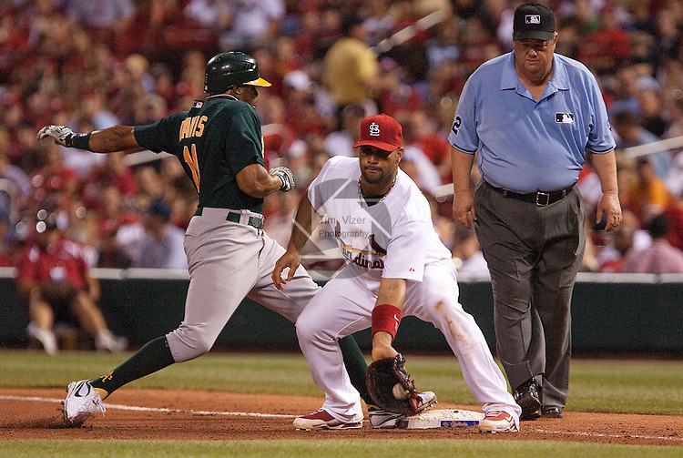 June 18, 2010       Oakland Athletics center fielder Rajai Davis (11) makes it safely back to first base on a pickoff throw to St. Louis Cardinals first baseman Albert Pujols (5).  Umpire watching is Joe West.  The St. Louis Cardinals defeated the Oakland Athletics 6-4 in the first game of a three-game homestand at Busch Stadium in downtown St. Louis, MO on Friday June 18, 2010.