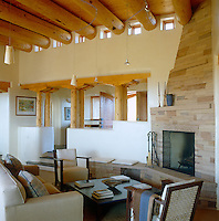 In the living room of this New Mexico house large circular pine logs have been used for the construction of the ceiling and Arizona flagstones for the fireplace