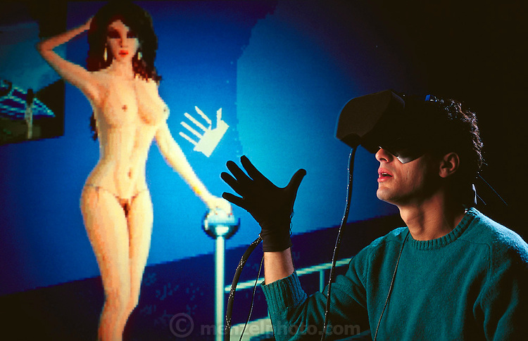 Virtual sex. Pornographic application of virtual reality, showing a man mauling his virtual conquest provided by his headset and data glove & an unseen computer system. Virtual, in computer parlance, describes equipment or programs that assume one form yet give the illusion of another. Here, the image of the woman is provided by the system through goggles in the head-set; contact is effectively faked by optic-optic sensors in the black, rubber data glove, which relay information on aspect and movement of the man's fingers. Photographed at Autodesk Inc., USA. MODEL RELEASED. (1990)