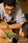 Preschool New York City ages 4-5 male high school student volunteering in classroom working with boy on project