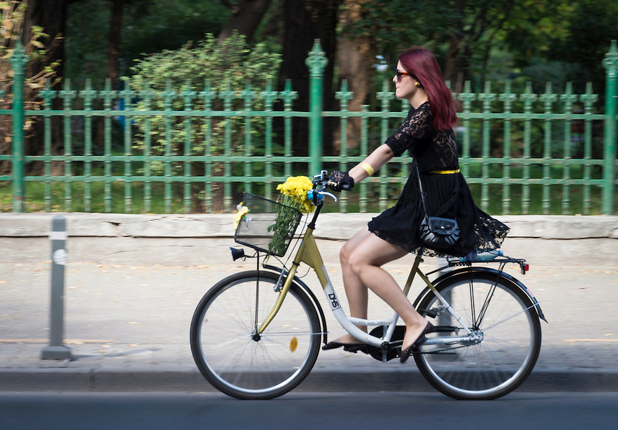 BUCHAREST, ROMANIA - September 30, 2012: Woman riding a bicycle outside the Cismigiu Gardens in Downtown Bucharest