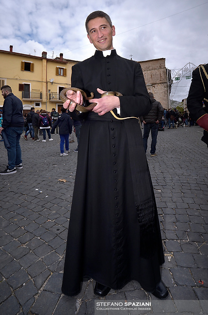 "The parish priest  of Cocullo with snakes in hand before the procession.The feast of snakes. Process dedicated to the Saint Dominic, in the streets of Cocullo, in the Abruzzo region, Italy on May 1, 2019.<br /> <br /> <br /> <br /> The St. Domenico's procession in Cocullo, central Italy. Every year on the first  of May, snakes are placed onto the statue of St. Domenico and then the statue is carried in a procession through the town. St. Domenico is believed to be the patron saint for people who have been bitten by snakes:<br /> <br /> Italy, Cocullo, in the Province of L'A...quila, is at 870 meters a.s.l., along the railway line connecting Sulmona to Rome. The village rises alongside Mount Luparo (1327 meters) ""The valley opening in front of the village is surrounded by bare rocks, while on the other side, to the south, snow-capped mountain crests follow one after the other...""<br /> San Domenico Abate lived in the 10th and 11th centuries AD. Born in Foligno, in the Umbria region, he started his pilgrimages, preaching and ascetic practices in Central Italy, making miracles recorded by the word-of-mouth tradition. He died on 22 January 1031 and was buried in Sora.<br /> <br /> Cocullo snake charmers are over with their snake hunting. They proceeded through the During the procession on the first in May, before the snakes are placed all over the statue of St. Dominick, they will be fed with milk kept in containers with crusca. It is the snake that, most of all other elements, expresses an ancestral myth: the unknown aspect and unpredictability of the natural environment with man's innate need to achieve the dominance on his own habitat. <br /> <br /> Snakes and wolves were the emblems of Italic peoples like the Marsians and Irpinians. Some areas in Abruzzo, especially in the Sagittario valley, were under the menace of wolves and snakes, which for the local populations represented the uncertainty and anxiety of their existence that, together with the precariousness and hardships of life, were almost unbearable. Therefore the community"