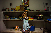 Mathumita's son waits for his mother to get his clothes in their house in Punaineeravi village in Kilinochchi in Northern Sri Lanka. Photo: Sanjit Das/Panos