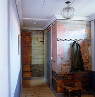 Peeling layers of wallpaper reveal the wooden walls in this entrance hall