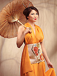 Beautiful asian woman wearing an orange dress stading with an umbrella in her hand
