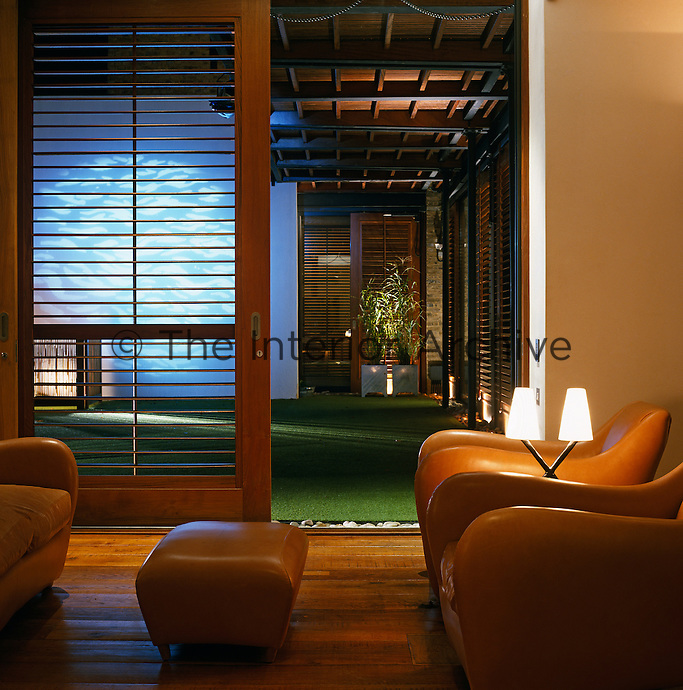 Seen through the open door of the living room, the courtyard garden is lit by recessed lights behind bamboo screens