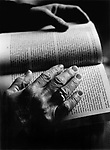 A person with wrinkled hands reading a book