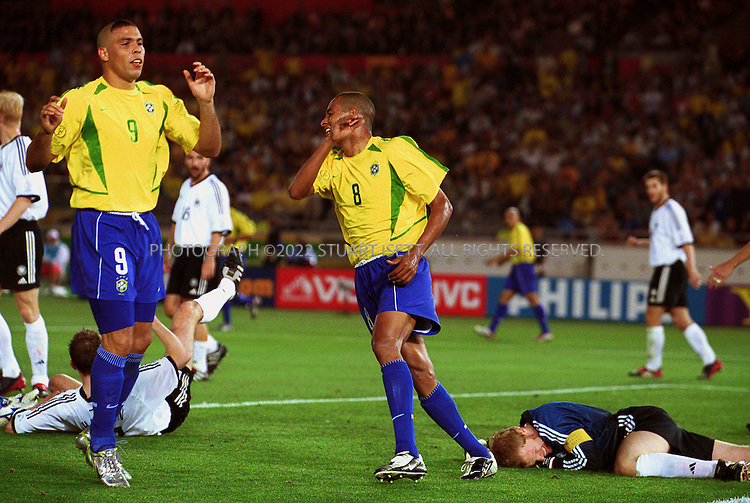 6/30/2002--Yokohama, Japan..Ronaldo and Silva Gilberto react after missing a goal opportunity in the 51st of the second half while Germany's captain and gaolie Oliver Kahn lies injured on the ground. .Brazil beat Germany 2-0 to win the World Cup...All photographs ©2003 Stuart Isett.All rights reserved.This image may not be reproduced without expressed written permission from Stuart Isett.