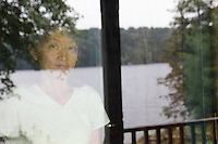 Hortonia, VT, USA - August 21, 2011: Reflection in cabin window of a lake as a woman looks out