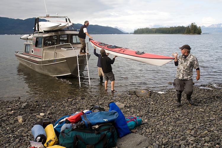Alaska, Prince William Sound, Sea kayakers, Lazy Otter Charters, boat shuttle, USA, Sea kayakers unloading camping gear, kayaks,