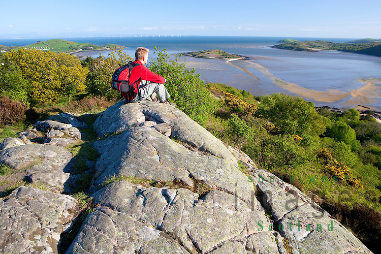 Walking walker sitting above Rockcliffe and Kippford on Mark Hill admiring view out to Rough Island and Robin Rigg wind farm in the Solway Firth Dumfries and Galloway Scotland UK