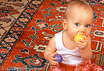9 month old baby girl sitting holding different colored wooden balls mouthing or biting one of them horizontal caucasian