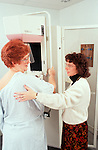 Medical technician prepares woman for mammogram