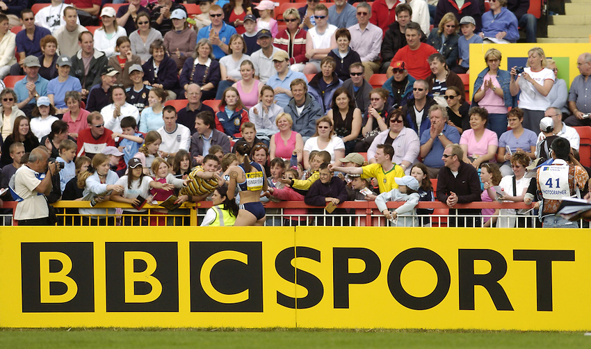 Photo. Jed Wee..Norwich Union British Grand Prix, 27/06/2004..Russia's Yelena Isinbayeva signs autographs after her world record, with BBC Sport board.