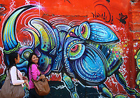 Two girls walk by vibrant street art in Bogota, Colombia, where graffiti is abundant.