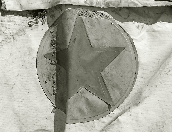 A star on a discarded fairground tarp.