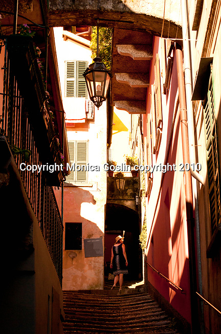 A woman walks up a path between houses in Varenna, Italy; a town on Lake Como