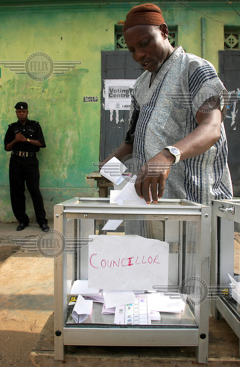 A man votes in the local government elections for Councillor and Chairman. Nigeria has been a democracy since 1999.