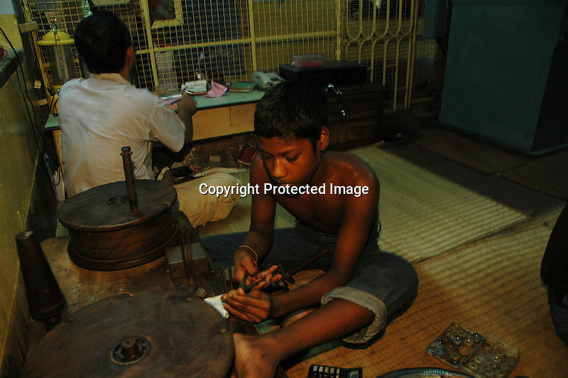 An Indian young boy working with a golden string to make it  much finer so that it can be used to make gold ornaments. Kolkata, India  6/13/2007  Arindam Mukherjee