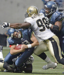 Seahawks' quarterback Matt Hasselbeck is sacked by Saints' defenders Charles Grant (94) and Willie Whitehead (98) during the second quarter on Sunday, Sept. 7, 2003 at Seahawks' Stadium. Even through being sacked, Hasselbeck completed 12 of 23 passes for 137 yards and two touchdowns, leading the Seahawks over the Saints 27-10. Jim Bryant Photo
