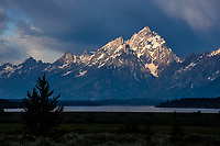 Morning storm clouds fill the sky as the sun's first rays of the morning illuminate the Grand Teton.