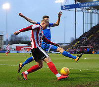 Lincoln City's Danny Rowe crosses the ball despite the attentions of Notts County's Shaun Brisley<br /> <br /> Photographer Chris Vaughan/CameraSport<br /> <br /> The EFL Sky Bet League Two - Lincoln City v Notts County - Saturday 13th January 2018 - Sincil Bank - Lincoln<br /> <br /> World Copyright &copy; 2018 CameraSport. All rights reserved. 43 Linden Ave. Countesthorpe. Leicester. England. LE8 5PG - Tel: +44 (0) 116 277 4147 - admin@camerasport.com - www.camerasport.com
