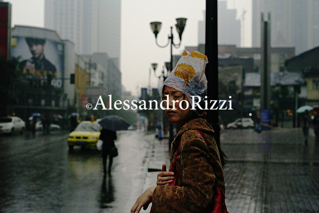 A woman out in the rain, near the JW Marriott Hotel, in Chongqing. The city of Chongqing is one of the fastest-growing urban centres on the planet. It is changing ferociously rapidly, its economic growth is astounding and it is attracting hordes of people looking for riches but it is also suffering from high pollution and a huge income gap. It is by some measures already the world's largest city, with 32 million inhabitants, although most are peasants who live within newly redrawn municipal limits