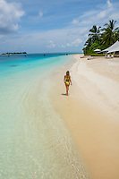 Maldives, Rangali Island. Conrad Hilton Resort. Woman walking on the talcum powder white sand beach.