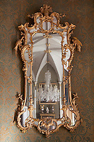 The gothic vaulted ceiling of the grand music room reflected in an older rococo gilt-framed mirror