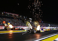 Feb 7, 2014; Pomona, CA, USA; Sparks fly from the headers of NHRA top fuel dragster driver Steve Faria (near lane) as he races alongside Clay Millican during qualifying for the Winternationals at Auto Club Raceway at Pomona. Mandatory Credit: Mark J. Rebilas-