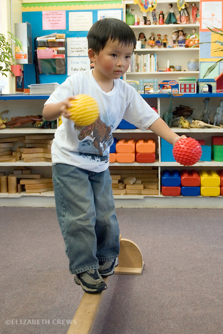 Berkeley CA  Preschool boy practicing balancing on balance beam in class.