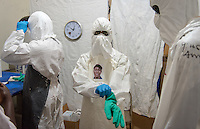 "Health care worker Joseph W. Walatee dons his PPE, complete with his photo, as he prepares to enter the ""red zone"" to care for patients at the ELWA II Ebola Treatment Unit (ETU) in Monrovia, Liberia on Sunday, March 1, 2015. Occidental College professor Mary Beth Heffernan's PPE Portrait Project involves photographing health care workers and making disposable, adhesive prints of their images, which are then placed on the worker's PPE.<br /> (Photo by Marc Campos, Occidental College Photographer) Mary Beth Heffernan, professor of art and art history at Occidental College, works in Monrovia the capital of Liberia, Africa in 2015. Professor Heffernan was there to work on her PPE (personal protective equipment) Portrait Project, which helps health care workers and patients fighting the Ebola virus disease in West Africa.<br />