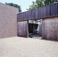 The entrance to the property is concealed behind a high wooden gate leading off a gravel parking area