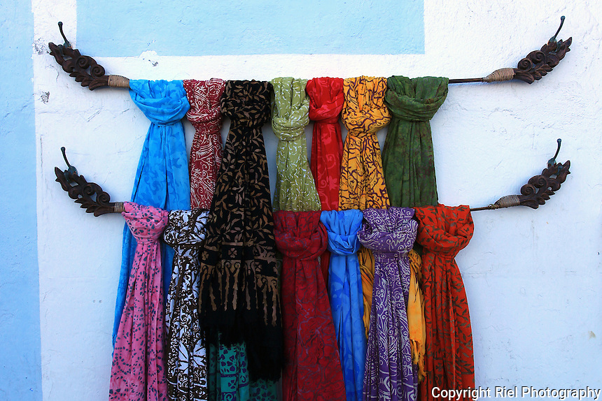 Colorful scarves displayed outside a Spanish shop.