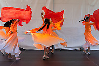 Girls wearing beautiful orange dresses dancing Chinese Red Fan Dance, Northwest Folklife Festival 2016, Seattle Center, Washington, USA.