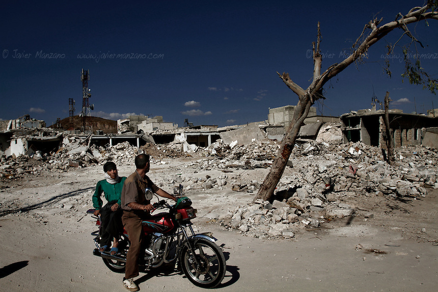 Residents of the northern Syrian town of Az'az stop to survey the remains of homes destroyed by a bomb dropped by a regime jet in early August, 2012...© Javier Manzano